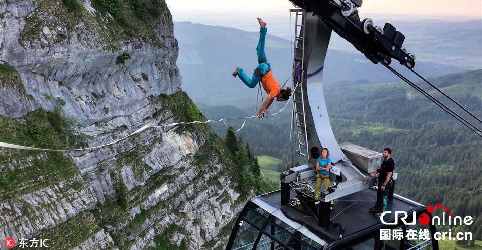 瑞士男子和女友高山缆车间走扁带 高空惊险玩倒立